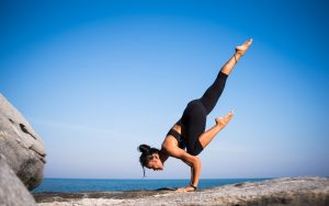 woman doing yoga on rocks with ocean view